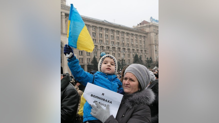 A woman holds a sign that reads: 'I am Volnovakha' as a child holds up a Ukrainian flag during a rally on Independence Square in Kiev, Ukraine, in solidarity with the victims of a rocket attack this week that claimed 13 lives on a highway near the eastern town of Volnovakha, on Sunday, Jan. 18, 2015. Ukraine's government accuses Russian-backed separatists of launching the rocket attack, which hit a passenger bus, but the rebels have rejected that charge. (AP Photo/Efrem Lukatsky)