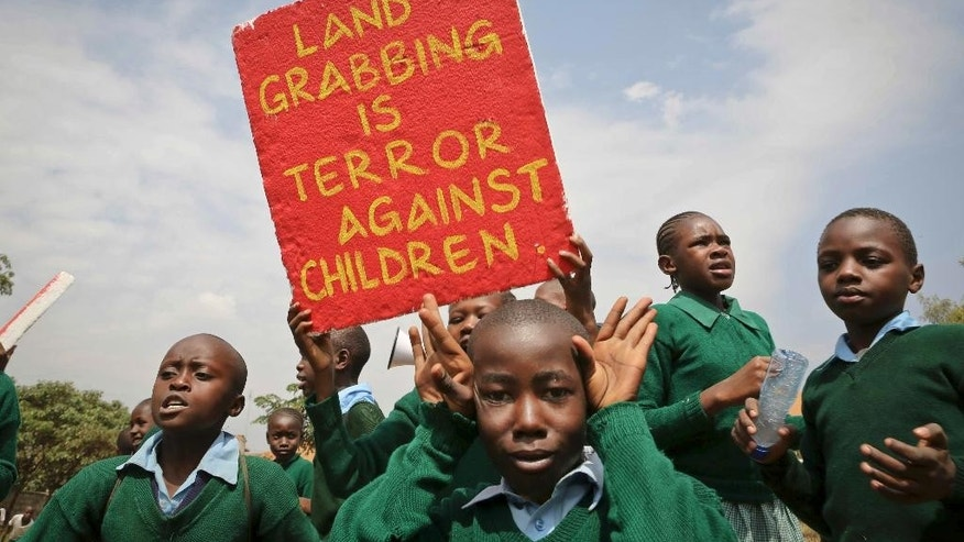 Kenyan school pupils hold up a placard brought by activists during a protest against the removal of their school's playground, at the Langata Road Primary School, in Nairobi, Kenya Monday, Jan. 19, 2015. Kenyan police tear-gassed schoolchildren demonstrating against the removal of their school's playground, the land of which has been allegedly grabbed by a powerful politician, according to a Kenyan human rights activist. (AP Photo/Brian Inganga)