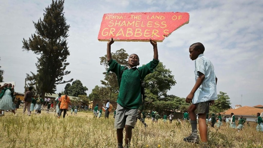 A Kenyan school pupil holds up a placard brought by activists during a protest against the removal of their school's playground, at the Langata Road Primary School, in Nairobi, Kenya Monday, Jan. 19, 2015. Kenyan police tear-gassed schoolchildren demonstrating against the removal of their school's playground, the land of which has been allegedly grabbed by a powerful politician, according to a Kenyan human rights activist. (AP Photo/Brian Inganga)