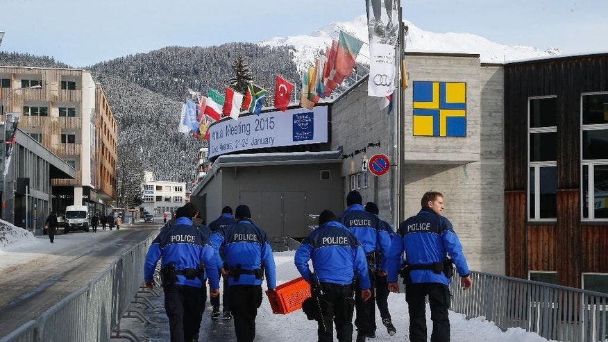 Swiss police officers walk past the Congress Hall in Davos, Switzerland, Monday, Jan. 19, 2015. The world's financial and political elite will head this week to the Swiss Alps for 2015's gathering of the World Economic Forum at the Swiss ski resort of Davos. (AP Photo/Michel Euler)
