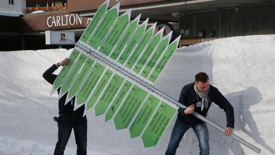 Technicians setting up signs outside the Congress Hall in Davos, Switzerland, Monday, Jan. 19, 2015. The world's financial and political elite will head this week to the Swiss Alps for 2015's gathering of the World Economic Forum at the Swiss ski resort of Davos. (AP Photo/Michel Euler)