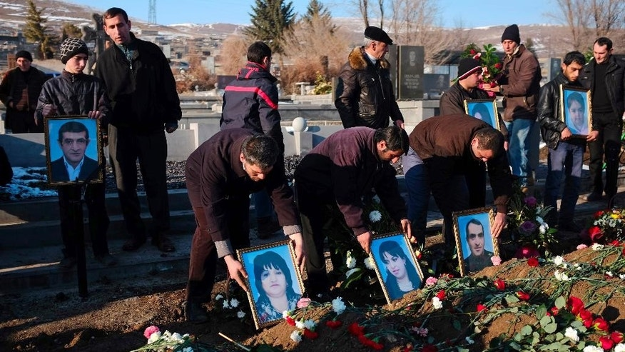 People holds portraits of six dead members of the Avetisyan family during a funeral in the city of Gyumri, Armenia, Thursday, Jan. 15, 2015. Armenian officials suspect a  Russian soldier of shooting a family of six dead at their home Gyumri early Monday. Police in Armenia have clashed Thursday with protesters demanding the handover of a Russian soldier suspected of murdering a family to Armenian authorities. (AP Photo/PAN Photo, Vahan Stepanyan)