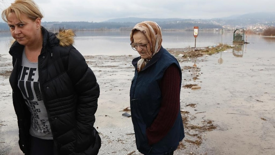Bosnian women walk thorough flood water in the Sarajevo suburb of Doglodi, Bosnia, Monday, Jan. 19, 2015. Heavy overnight rainfall has caused rivers in the Sarajevo area to rise and flood homes in the suburbs for the fifth time in the past 20 months. (AP Photo/Amel Emric)
