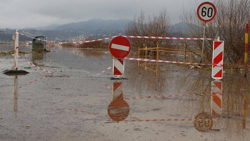 Road signs mark out an area of flooded water in the Sarajevo suburb of Doglodi, Bosnia, Monday, Jan. 19, 2015. Heavy overnight rainfall has caused rivers in the Sarajevo area to rise and flood homes in the suburbs for the fifth time in the past 20 months. (AP Photo/Amel Emric)