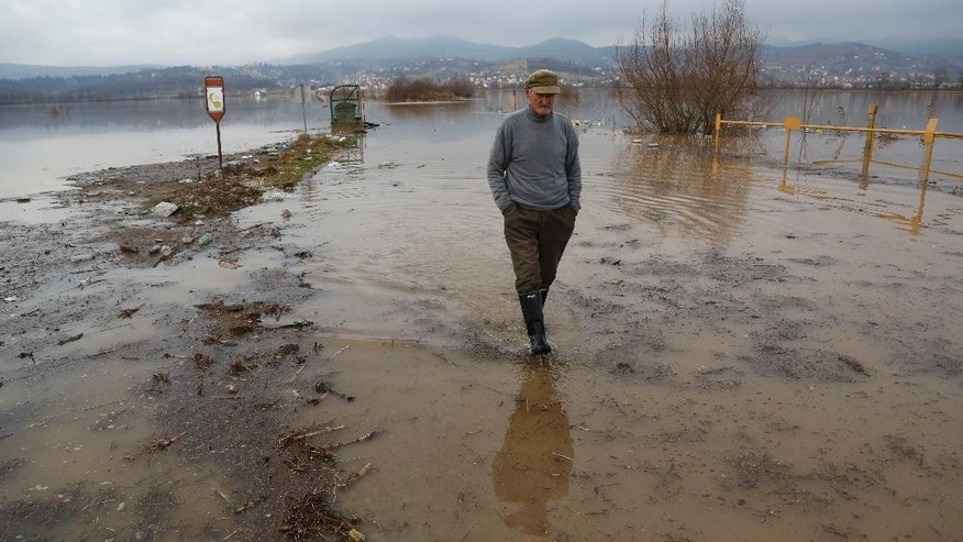 A Bosnian man walks thorough flood water in the Sarajevo suburb of Doglodi, Bosnia, Monday, Jan. 19, 2015. Heavy overnight rainfall has caused rivers in the Sarajevo area to rise and flood homes in the suburbs for the fifth time in the past 20 months. (AP Photo/Amel Emric)
