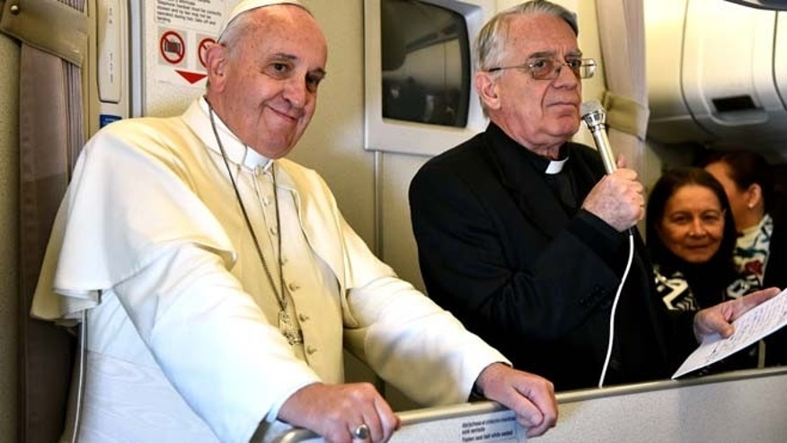 Jan. 19, 2015: Vatican spokesman Rev. Federico Lombardi, right, flanked by Pope Francis, talks with journalists during the flight from Manila to Rome. (AP/Giuseppe Cacace, pool)