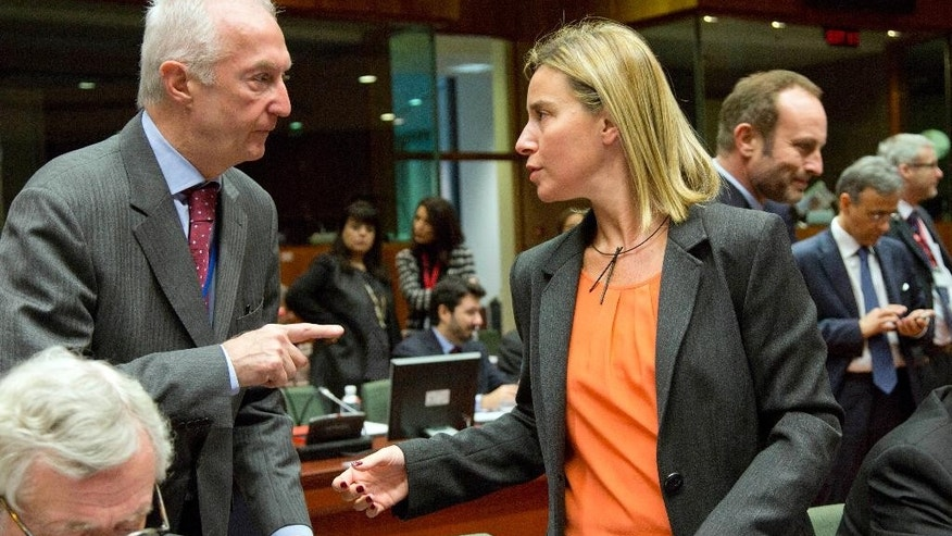 EU Counter-Terrorism chief Gilles de Kerkhove, left, gestures while speaking with European Union High Representative Federica Mogherini, center, during a meeting of EU foreign ministers in Brussels on Monday, Jan. 19, 2015. The European Union is calling for an anti-terror alliance with Arab countries to boost cooperation and information sharing in the wake of deadly attacks and arrests across Europe linked to foreign fighters. (AP Photo/Virginia Mayo)