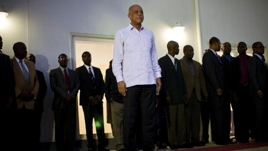 Haiti's President Michel Martelly listens to musicians play the presidential anthem after swearing-in his new Cabinet at the National Palace in Port-au-Prince, Haiti, Monday, Jan. 19, 2015. Ministers and secretaries of state were named roughly a week after parliament dissolved amid a bitter stalemate between Martelly and a group of opposition lawmakers. Martelly kept half of his former Cabinet ministers in their posts and made changes in several key ministries, including justice and planning. (AP Photo/Dieu Nalio Chery)