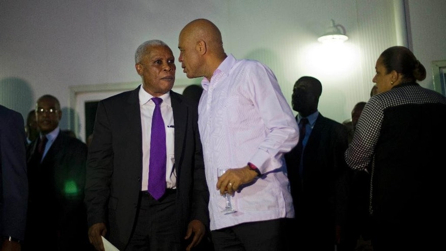 Haiti's President Michel Martelly, right, speaks with Public Works Minister Jacques Roussau after swearing-in his new Cabinet at the National Palace in Port-au-Prince, Haiti, Monday, Jan. 19, 2015. Ministers and secretaries of state were named roughly a week after parliament dissolved amid a bitter stalemate between Martelly and a group of opposition lawmakers. Martelly kept half of his former Cabinet ministers in their posts and made changes in several key ministries, including justice and planning. (AP Photo/Dieu Nalio Chery)
