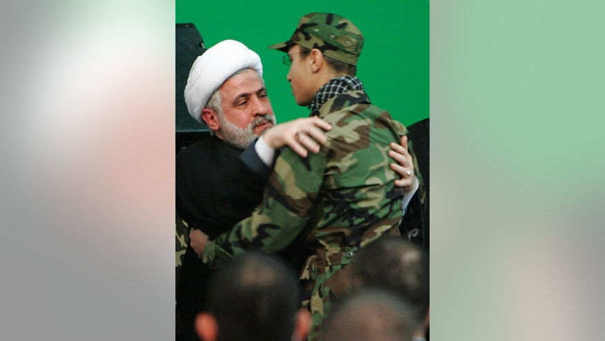 FILE - In this Feb. 22, 2008, file photo, Hezbollah Deputy Leader Sheikh Naim Kassem, left, greats Jihad Mughniyeh, the son of slain top Hezbollah commander Imad Mughniyeh, during a rally to commemorate Imad and two other leaders Abbas Musawi and Ragheb Harb in the Shiite suburb of Beirut, Lebanon. A Hezbollah official said Sunday, Jan. 18, 2015, that an Israeli strike in the Syrian Golan Heights killed Jihad Mughniyeh and four other fighters from the Lebanese Shiite militant group. (AP Photo/Hussein Malla, File)
