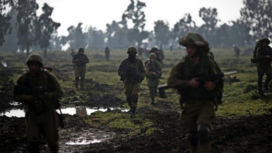 Israeli soldiers of the Golani brigade march during training in the Israeli controlled Golan Heights, near Israel-Syria border, Monday, Jan. 19, 2015. The Lebanese militant Hezbollah on Monday prepared to bury six core fighters killed in Syria the day before in what the group described as an Israeli airstrike, including the son of a slain Hezbollah military chief — the group's most prominent figure to die so far in the conflict next door. Although Israel did not confirm or deny the strike, it was a serious blow to Hezbollah, stretched thin and neck-deep in Syria's civil war where the group's Shiite fighters are battling alongside President Bashar Assad's forces. Tehran has confirmed that an Iranian Gen. Mohammad Ali Allahdadi was among the seven killed. (AP Photo/Ariel Schalit)