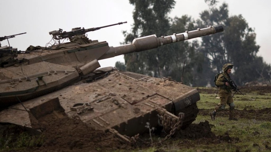 An Israeli soldiers of the Golani brigade trains in the Israeli controlled Golan Heights, near Israel-Syria border, Monday, Jan. 19, 2015. The Lebanese militant Hezbollah on Monday prepared to bury six core fighters killed in Syria the day before in what the group described as an Israeli airstrike, including the son of a slain Hezbollah military chief — the group's most prominent figure to die so far in the conflict next door. Although Israel did not confirm or deny the strike, it was a serious blow to Hezbollah, stretched thin and neck-deep in Syria's civil war where the group's Shiite fighters are battling alongside President Bashar Assad's forces. Tehran has confirmed that an Iranian Gen. Mohammad Ali Allahdadi was among the seven killed. (AP Photo/Ariel Schalit)