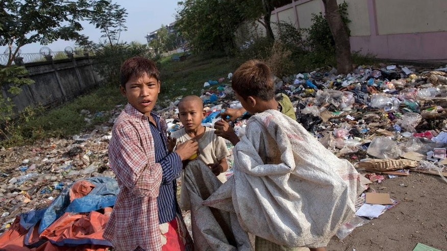 Dec. 22, 2014: Street children with glue-tins in their hands stand in the foreground of a roadside garbage dump in Hlaing Tharyar, northwest of Yangon, Myanmar. Since the lifting of Western sanctions, more than 500 foreign businesses have invested $50 billion in Myanmar.