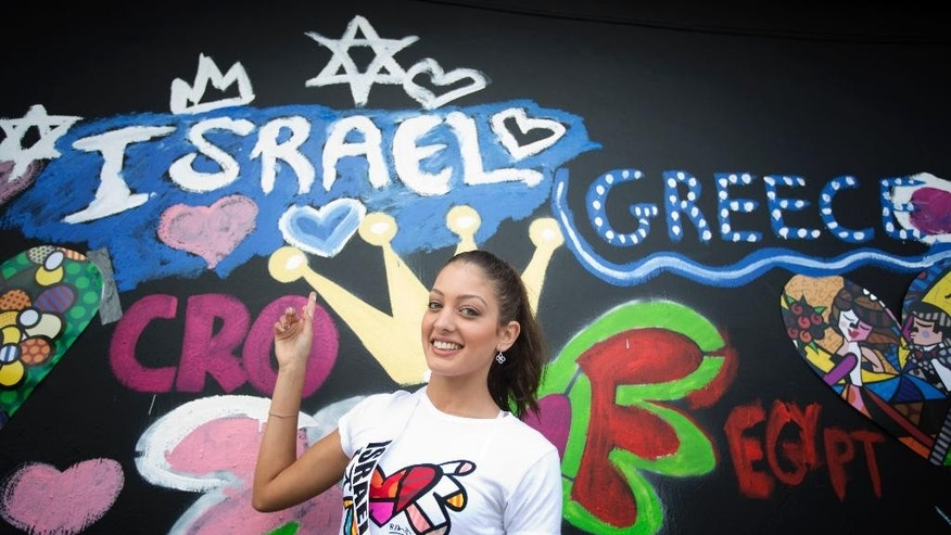 FILE - in this Sunday, Jan. 11, 2015 file photo, Miss Israel, Doron Matalon, poses for photos after she painted her country's name on a wall in Miami's Wynwood area. Explosive confrontations are nothing new for Israel and Lebanon, but the latest spat between the longtime foes is perhaps the first to have been caused by an alleged photo-bomb. A seemingly innocuous selfie at the Miss Universe pageant in Miami has sparked criticism in Lebanon because it featured a smiling Miss Lebanon alongside Miss Israel. The Israeli beauty queen, Doron Matalon, posted a picture of herself with colleagues from Japan, Slovakia and Lebanon on her Instagram account. The result? A formal Lebanese investigation into the scandal. (AP Photo/J Pat Carter, File)