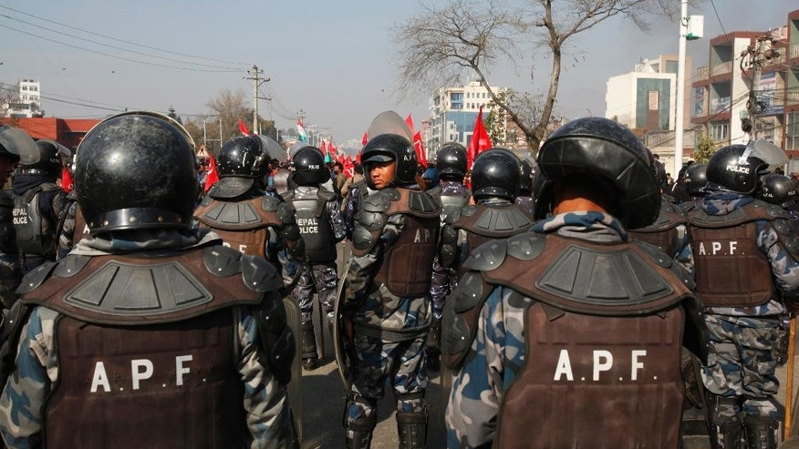 Nepalese Armed Police force stand guard near the Constitution Assemble during the general strike called by alliance of 30 party led by Communist Party of Nepal (CPN-Maoist) in Kathmandu, Nepal, Tuesday, Jan 20, 2015. Opposition parties staged general strike to shut down Nepal on Tuesday as opposition politicians threw chairs and attacked the parliamentary speaker in a bid to block the government from pushing through a draft of a new constitution. (AP Photo/Niranjan Shrestha)