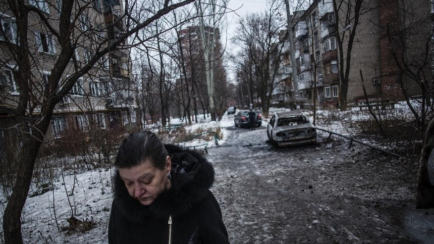 A woman walks through a residential area hit by the Ukrainian Army Artillery in Voroshilovsky area, center of Donetsk, Ukraine. Sunday, Jan. 18, 2015. The separatist stronghold, Donetsk, was shaken by intense outgoing and incoming artillery fire as a bitter battle raged for control over the city's airport. Streets in the city, which was home to 1 million people before unrest erupted in spring, were completely deserted and the windows of apartments in the center rattled from incessant rocket and mortar fire. (AP Photo/Manu Brabo)