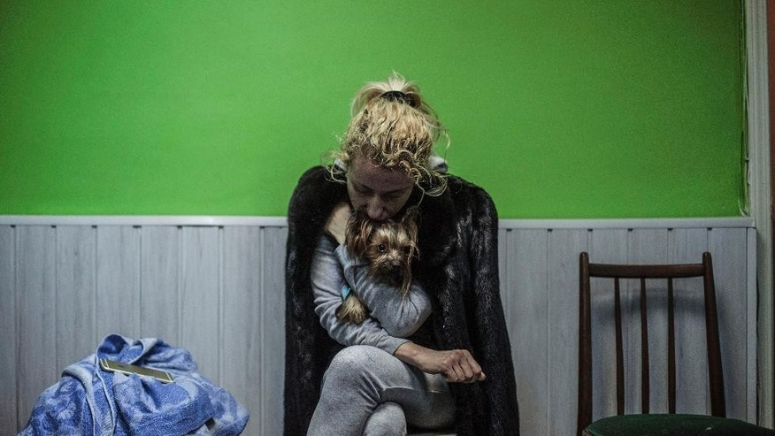 A Ukrainian woman embraces her dog in a shelter during the heaviest exchange of artillery fire in the last few days, at Voroshilovsky area, center of Donetsk, Ukraine. Sunday, Jan. 18, 2015. The separatist stronghold, Donetsk, was shaken by intense outgoing and incoming artillery fire as a bitter battle raged for control over the city's airport. Streets in the city, which was home to 1 million people before unrest erupted in spring, were completely deserted and the windows of apartments in the center rattled from incessant rocket and mortar fire. (AP Photo/Manu Brabo)