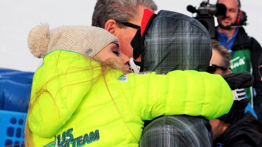 Tiger Woods and Lindsey Vonn, left, exchange a kiss in the finish area of an alpine ski, women's World Cup super-G, in Cortina d'Ampezzo, Italy, Monday, Jan. 19, 2015. Lindsey Vonn won a super-G Monday for her record 63rd World Cup victory and celebrated with an embrace from a surprise visitor, boyfriend Tiger Woods. The American broke Annemarie Moser-Proell's 35-year-old record of 62 World Cup wins with a flawless run down the Olympia delle Tofane course, finishing 0.85 ahead of Anna Fenninger of Austria. (AP Photo/Ivan Carabini)