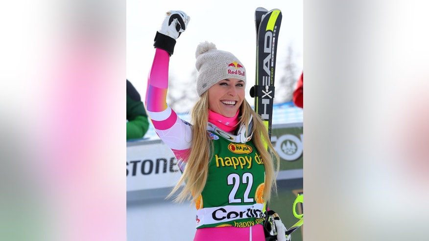 Lindsey Vonn celebrates after winning an alpine ski, women's World Cup super-G, in Cortina d'Ampezzo, Italy, Monday, Jan. 19, 2015. (AP Photo/Armando Trovati)