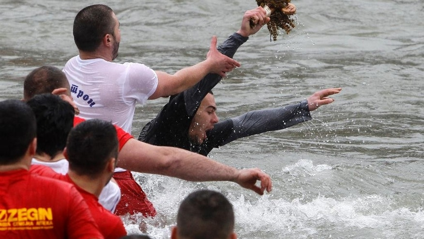 Macedonian Dusan Cimev, center, retrieves the wooden cross from Vardar River, cast by Macedonian Archbishop Stefan during the Epiphany ceremony in Skopje, Macedonia, on Monday, Jan. 19, 2015. Macedonian Orthodox Christians celebrate Epiphany across the country, commemorating the baptism of Christ according to the Julian calendar. (AP Photo/Boris Grdanoski)