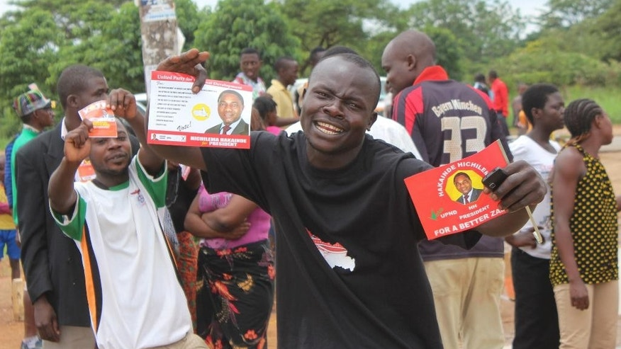 A supporter of Zambia's leading opposition United Party for National Development (UPND), led by Hakainde Hichilema, shows his campaign leaflets during an election rally in Lusaka Sunday, Jan. 18, 2015. Zambians go to the polls Tuesday, Jan. 20 to elect a new president Tuesday after the death of former president Michael Sata in October 2014. (AP Photo/Moses Mwape)