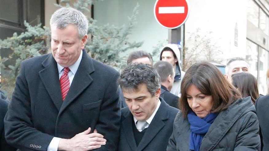 New York city mayor Bill de Blasio, left,  Paris mayor Anne Hidalgo, right,  and Patrick Pelloux, center, a staff member of Charlie Hebdo newspaper, react outside Charlie Hebdo offices, in Paris, Tuesday Jan.20, 2015. Brothers Said and Cherif Kouachi and their friend, Amedy Coulibaly, killed 17 people at the satirical newspaper Charlie Hebdo, a kosher grocery and elsewhere last week.(AP Photo/Francois Mori)