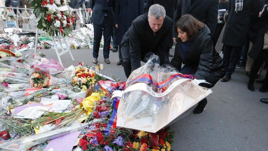New York city mayor Bill de Blasio and Paris mayor Anne Hidalgo, left, lay a wreath of flowers at the site of the Charlie Hebdo newspaper attack, in Paris, Tuesday Jan.20, 2015. Brothers Said and Cherif Kouachi and their friend, Amedy Coulibaly, killed 17 people at the satirical newspaper Charlie Hebdo, a kosher grocery and elsewhere last week.(AP Photo/Francois Mori)