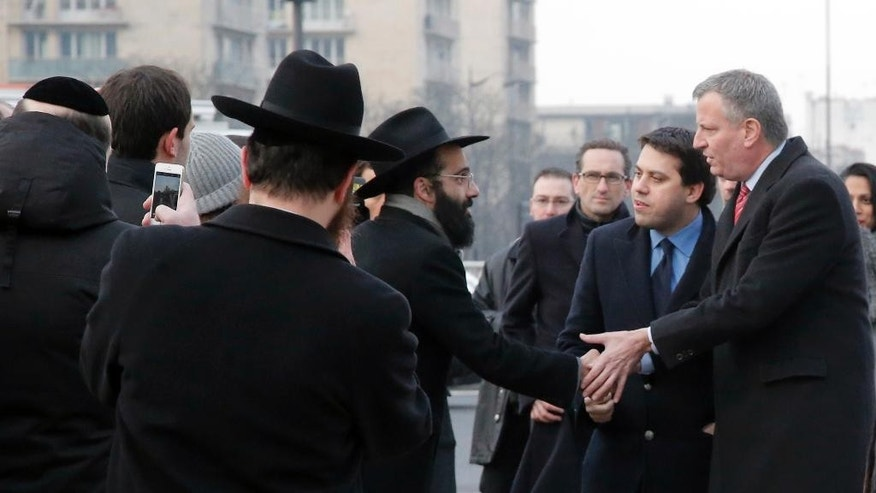 New York city mayor Bill de Blasio, right, greets Jewish community members prior to laying a wreath of flowers at the kosher grocery where Amedy Coulibaly killed four people in a terror attack, in Paris, Tuesday, Jan. 20, 2015. Coulibaly shot a policewoman to death on the outskirts of Paris and then seized hostages inside a kosher supermarket, killing four before he was killed by police. Yellow poster reads: Brave police officers and gendarmes, Thank you. (AP Photo/Francois Mori)