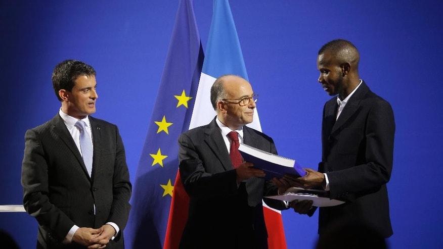 French Prime Minister Manuel Valls, left, and French Interior Minister Bernard Cazeneuve, center, award citizenship to Lassana Bathily during a ceremony  in Paris, Tuesday, Jan. 20, 2015. Bathily, a Muslim employee born in Mali, has been granted French citizenship and honored as a hero by France's authorities for saving lives during the attack of a kosher supermarket in Paris. (AP Photo/Christophe Ena)