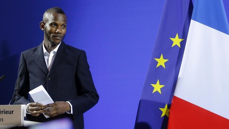 Lassana Bathily delivers his speech during a citizenship ceremony in Paris, Tuesday, Jan. 20, 2015. Bathily, a Muslim employee born in Mali, has been granted French citizenship and honored as a hero by France's authorities for saving lives during the attack of a kosher supermarket in Paris. (AP Photo/Christophe Ena)