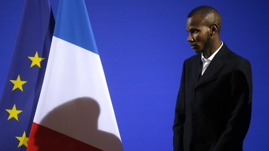 Lassana Bathily listens to French Interior Minister Bernard Cazeneuve as he attends a citizenship ceremony in Paris, Tuesday, Jan. 20, 2015. Bathily, a Muslim employee born in Mali, has been granted French citizenship and honored as a hero by France's authorities for saving lives during the attack of a kosher supermarket in Paris. (AP Photo/Christophe Ena)