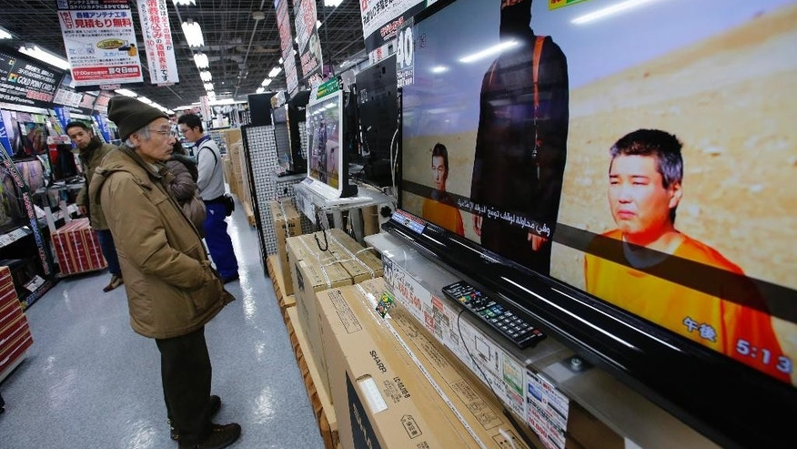 A man watches a television broadcasting a news about detained two Japanese, at an electronics store in Tokyo, Tuesday, Jan. 20, 2015. The release of an online video Tuesday purporting to show an Islamic State figure demanding $200 million in ransom for two Japanese hostages ambushed Prime Minister Shinzo Abe as he was wrapping up a six-day tour of the Middle East. (AP Photo/Shizuo Kambayashi)