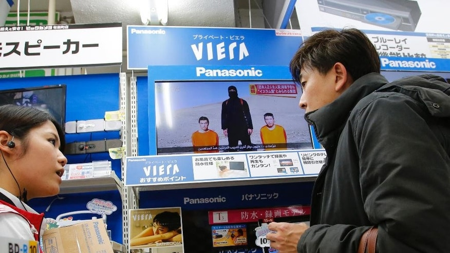 A shopper chats with a sales clerk with a television broadcasting a news about detained two Japanese in the background, at an electronics store in Tokyo, Tuesday, Jan. 20, 2015. The release of an online video Tuesday purporting to show an Islamic State figure demanding $200 million in ransom for two Japanese hostages ambushed Prime Minister Shinzo Abe as he was wrapping up a six-day tour of the Middle East. (AP Photo/Shizuo Kambayashi)
