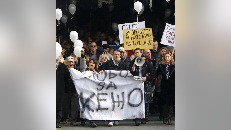 Macedonian journalist Tomislav Kezarovski, center, marches with his colleagues and friends during a protest through a street in Skopje, Macedonia, Tuesday, Jan. 20, 2015. Tomislav Kezarovski was released from jail conditionally due to unspecified health problems Tuesday and joined a couple of thousand of people demonstrating outside the appeals court in his support and demanding more press freedom. The banner in the bottom reads Freedom for Kezo (Kezarovski). (AP Photo/Boris Grdanoski)