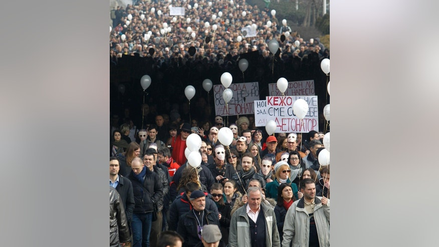 Protestors march in support of a jailed journalist, through a street in Skopje, Macedonia, Tuesday, Jan. 20, 2015.   Macedonian media said  journalist Tomislav Kezarovski recently jailed after an appeals court upheld his conviction for revealing the identity of a protected witness has been granted temporary release because of health problems. Tomislav Kezarovski left jail Tuesday and joined about 2,000 people demonstrating outside the appeals court in his support and demanding more press freedom. (AP Photo/Boris Grdanoski)