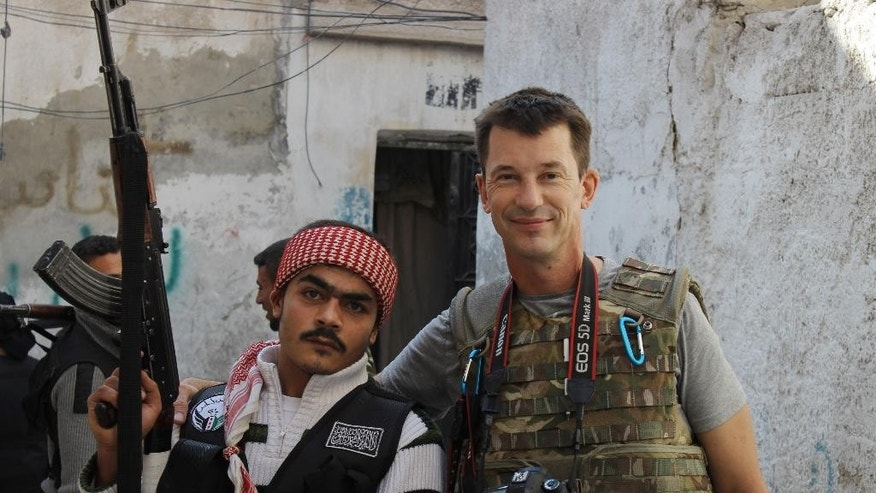 FILE - In this Nov. 11, 2012 file photo, freelance British photojournalist John Cantlie poses with a Free Syrian Army rebel in Aleppo, Syria. The British photojournalist has been used by the Islamic State group to take on the role of a war correspondent. He has appeared in several videos delivering statements, purportedly from Kobani and Mosul, likely under duress. Cantlie has worked for several publications including The Sunday Times, The Sun and The Sunday Telegraph, and was kidnapped with American journalist James Foley in November 2012. IS militant beheaded Foley in August, 2014. (AP Photo, File)