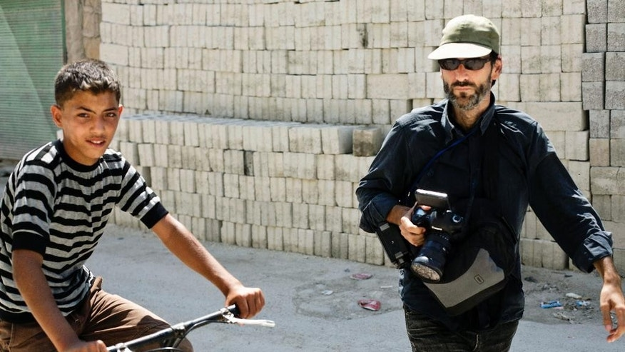 FILE - This undated file picture released by the family of Ricardo Garcia-Vilanova, shows Spanish photographer Ricardo Garcia-Vilanova, right, walking next to a Syrian boy riding a bike in Aleppo, Syria. The Islamic State group has released several hostages, reportedly in exchange for ransom money. Three Spanish journalists were released in March after being held hostage for months. (AP Photo/Ricardo's Family, FIle)