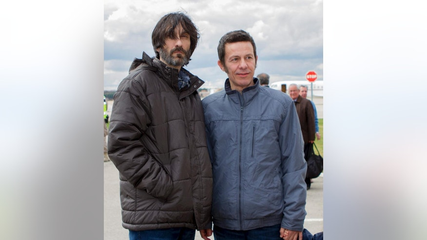 FILE - In this Sunday, March 30, 2014 file photo, Spanish reporters Javier Espinosa, right, and Ricardo Garcia Vilanova, left, pose upon their arrival at the military airbase in Torrejon de Ardoz, Madrid, Spain. The Islamic State group has released several hostages, reportedly in exchange for ransom money. Espinosa and Vilanova were released in March after being held hostage for months. (AP Photo, File)