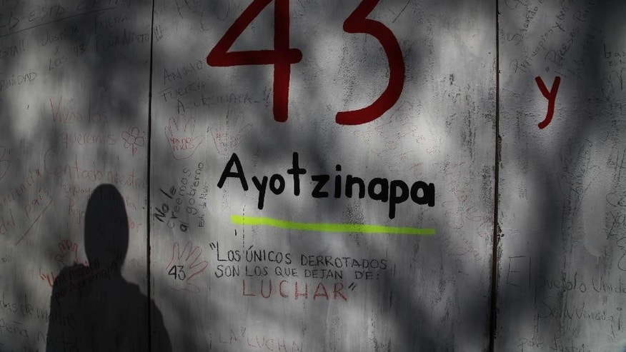 FILE - In this  Dec. 28, 2014 file photo, the shadow of a demonstrator is cast on a wall with graffiti protesting the disappearance of 43 rural college students, in front of the Mexican Attorney General's office, in Mexico City. Mexican prosecutors said Tuesday, Jan. 20, 2015, that an Austrian forensics lab has been unable to find any more DNA that could be used by conventional means to identify charred remains that might be those of missing college students, but said they have authorized a final, unconventional effort. (AP Photo/Marco Ugarte, File)