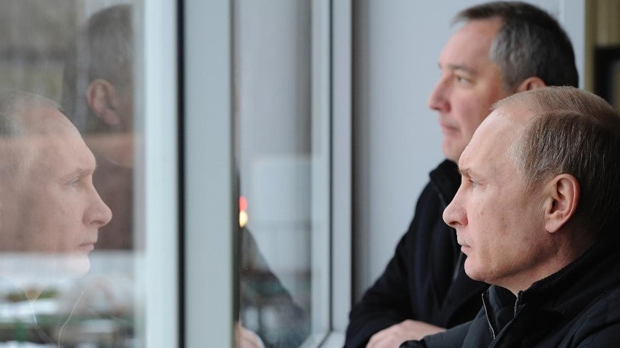 Russian President Vladimir Putin, right, visits the Central Scientific Research Institute of Precise Mechanical Engineering in Klimovsk, near Moscow, Russia, Tuesday, Jan. 20, 2015. At rear  is Deputy Prime Minister Dmitry Rogozin. (AP Photo/RIA-Novosti, Mikhail Klimentyev, Presidential Press Service)