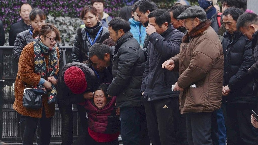 FILE - In this Tuesday, Jan. 6, 2015 file photo, a woman, third from left, grieves as she is comforted by other relatives of a New Year's Eve stampede victim at the site of the tragic accident in Shanghai, China. Shanghai sacked four top district officials for insufficient preparation and response to the stampede that killed 36 people, the city government announced Wednesday, Jan. 21. 2015. Investigation results released by the Shanghai government also noted that some of the officials responsible were at an opulent banquet the night of the disaster, hampering the response and adding to public discontent. (AP Photo, File) CHINA OUT