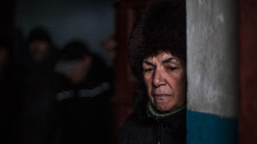 A Ukrainian woman waits for shelling to abate as she shelters inside a building after a Ukrainian army shell hit a bus stop in the Kievsky district in Donetsk, Ukraine, Tuesday, Jan. 20, 2015. At least three civilians were killed in shelling Tuesday in eastern Ukraine as fighting continued between government and rebel forces in the separatist-held city of Donetsk. (AP Photo/Manu Brabo)