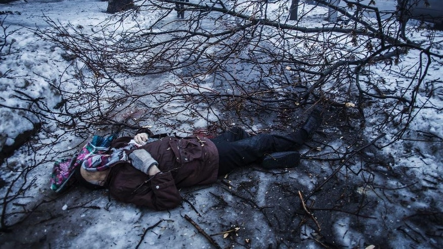 A person walk near the remains of a man lying near a bus stop that was damaged in shelling by the Ukrainian army in Donetsk, eastern Ukraine, Tuesday, Jan. 20, 2015. At least three civilians were killed in shelling Tuesday in eastern Ukraine as fighting continued between government and rebel forces in the separatist-held city of Donetsk. (AP Photo/Manu Brabo)