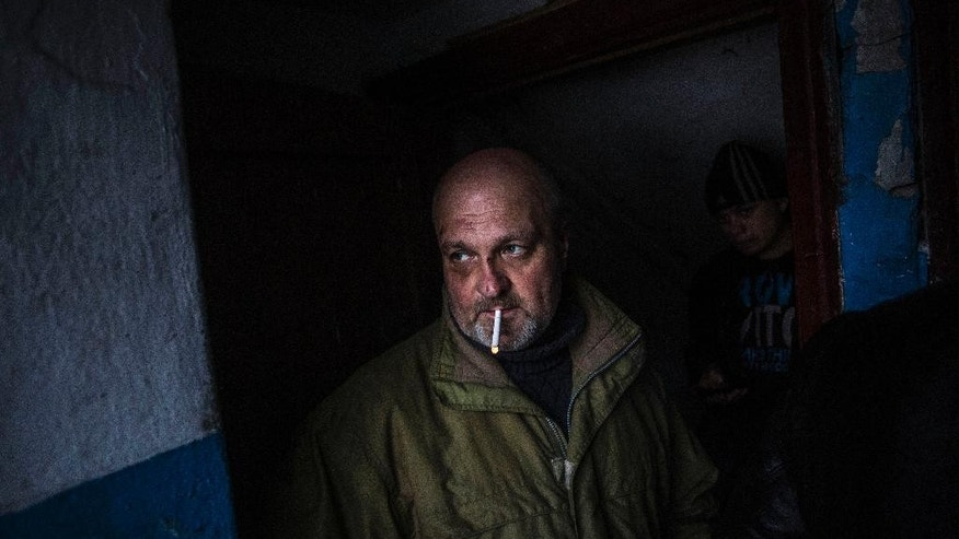 A Ukrainian man waits for shelling to abate as he shelters inside a building after a Ukrainian army shell hit a bus stop in the Kievsky district in Donetsk, Ukraine, Tuesday, Jan. 20, 2015. At least three civilians were killed in shelling Tuesday in eastern Ukraine as fighting continued between government and rebel forces in the separatist-held city of Donetsk. (AP Photo/Manu Brabo)