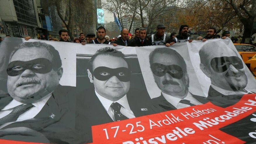 FILE - In this Dec. 17, 2014 file photo, lawmakers and officials from the main opposition Republican People's Party, CHP, carry posters with images of Turkey's former Economy Minister Zafer Caglayan, second right, former Urban Planning and Environment Minister Erdogan Bayraktar, right, former Interior Minister Muammer Guler, left, and former EU Affairs Minister Egemen Bagis on the first anniversary of a massive corruption and bribery scandal that they were allegedly involved in, during a protest in Ankara, Turkey. Turkey's parliament is preparing to vote on corruption allegations Tuesday, Jan. 20, 2015 against four former cabinet ministers, in what could be the final chapter of a graft investigation that once seemed to threaten the inner circle of President Recep Tayyip Erdogan.(AP Photo/File)
