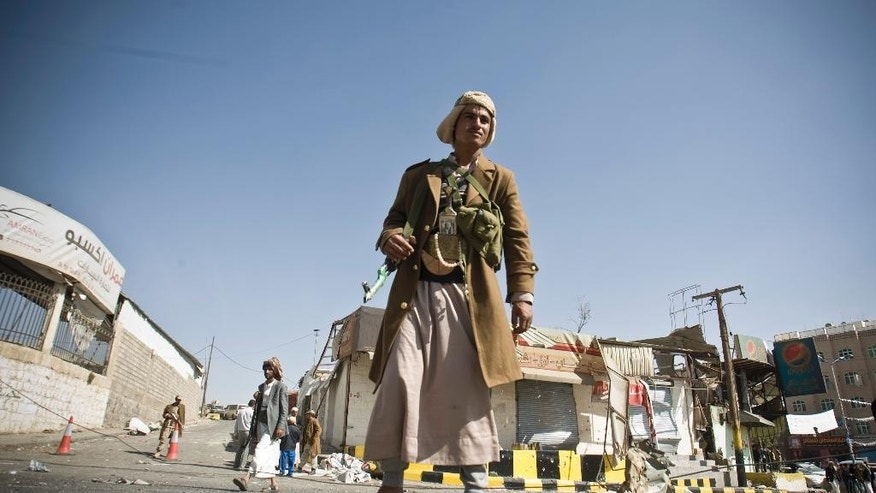 "A Houthi Shiite Yemeni stands guard in front of a building damaged during recent clashes near the presidential palace in Sanaa, Yemen, Tuesday, Jan. 20, 2015. Yemen's U.S.-backed leadership came under serious threat Monday as government troops clashed with Shiite rebels near the presidential palace and a key military base in what one official called ""a step toward a coup."" (AP Photo/Hani Mohammed)"