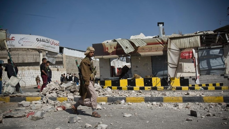 "A Houthi Shiite Yemeni walks past a building damaged during recent clashes near the presidential palace in Sanaa, Yemen, Tuesday, Jan. 20, 2015. Yemen's U.S.-backed leadership came under serious threat Monday as government troops clashed with Shiite rebels near the presidential palace and a key military base in what one official called ""a step toward a coup."" (AP Photo/Hani Mohammed)"