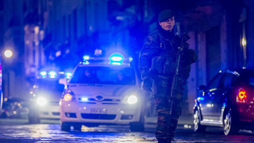 A Belgian security officer patrols near the Palace of Justice, where suspects wanted in Belgium on terrorism-related charges are set to appear before the federal court, in Brussels on Wednesday, Jan. 21, 2015. The suspects were picked up in an anti-terror sweep following a firefight in Verviers, in which two suspected terrorists were killed. (AP Photo/Geert Vanden Wijngaert)