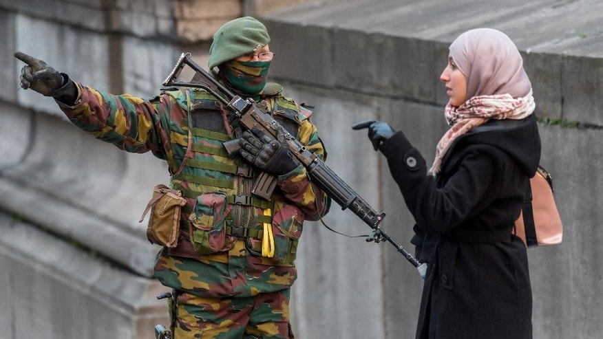 A Belgian security officer talks with a woman as he patrols near the Palace of Justice, where suspects wanted in Belgium on terrorism-related charges are set to appear before the federal court, in Brussels on Wednesday, Jan. 21, 2015. The suspects were picked up in an anti-terror sweep following a firefight in Verviers, in which two suspected terrorists were killed. (AP Photo/Geert Vanden Wijngaert)