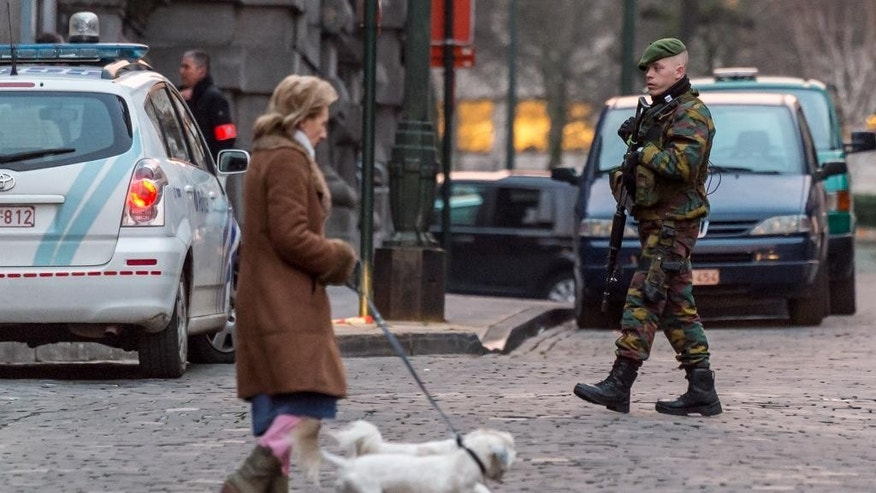 A woman walks with two dogs as a Belgian security officers patrols near the Palace of Justice, where suspects wanted in Belgium on terrorism-related charges are set to appear before the federal court, in Brussels on Wednesday, Jan. 21, 2015. The suspects were picked up in an anti-terror sweep following a firefight in Verviers, in which two suspected terrorists were killed. (AP Photo/Geert Vanden Wijngaert)